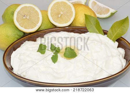homemade lemon mus with fresh lemons, decorated with lemon leaves and a lemon balm branch
