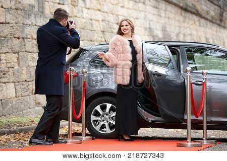 Beautiful young woman and photographer near car on red carpet, outdoors