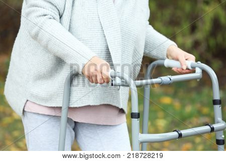 Elderly woman with walking frame outdoors, closeup