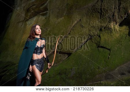 Horizontal portrait of a female medieval archer wearing green cloak resting outdoors walking through the woods with a bow in her hand copyspace hunting hunter Amazons tribes cosplay.