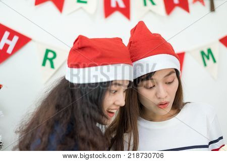 Two asia woman surprise when open gold gift box at holiday party with decoration flag at backgroundgiving Christmas party presentwow feeling and happiness momentlesbian lgbt couple lifestyle