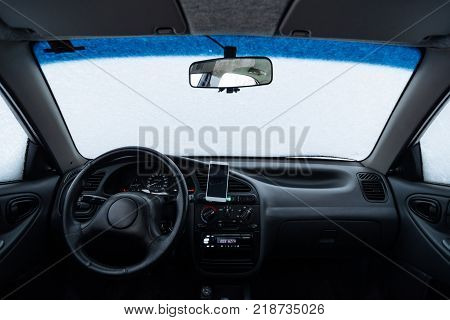 Windshield of the car covered with snow inside view
