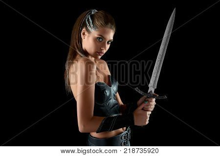 Horizontal studio portrait of a stunning young fearless female warrior posing with a sword on black background battle fighter bravery feminine femininity beauty courage Amazons tribe .
