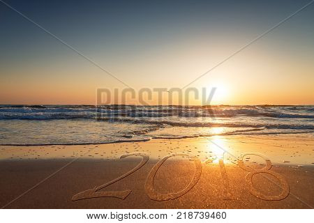 2018 written on the sand of a beach travel 2018 new year concept.