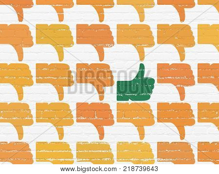 Social media concept: rows of Painted orange thumb down icons around green thumb up icon on White Brick wall background