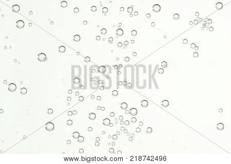 Many small shiny air bubbles over a light background