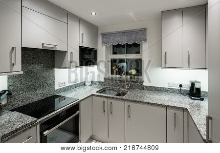 Small modern kitchen in UK apartment with granite and new appliances including induction cooktop