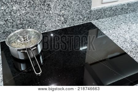 Water and potatoes boiling in stainless steel pan on modern induction hob or cooktop