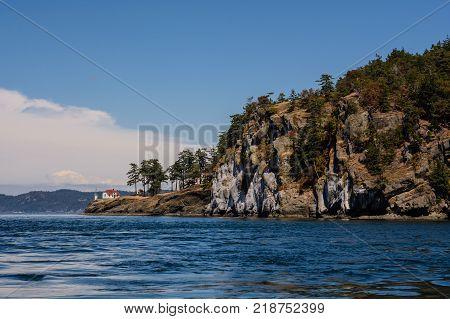 A lighthouse on the shore. The sun illuminates the forest the house of the lighthouse keeper and the shore.