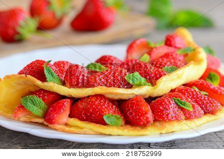 Red strawberry omelet. Fried omelet filled with fresh strawberries slices and garnished with green mint on a served plate. Sweet dessert omelet idea. Closeup