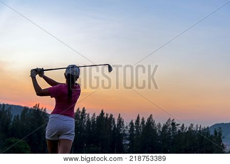 Asian woman Golf player hit swing shot golf ball on the green sunset of green club in eventing time. Healthy and Lifestyle Concept.
