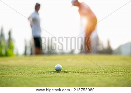 Golf ball approach to the hold on the green. Couple golf player putting golf ball in the background. Lifestyle Concept.