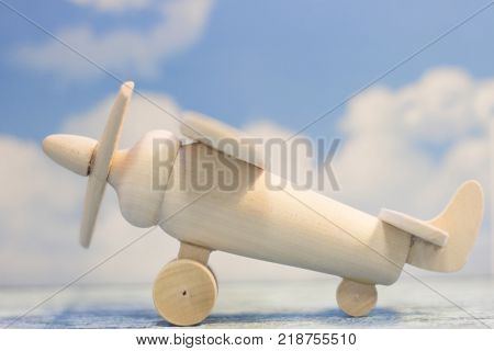 Travel concept. Fly abroad. A wooden toy airplane on a sky image background. Close up