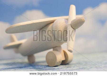 Travel and tourism concept. Fly abroad. A wooden toy airplane on a sky image background. Close up