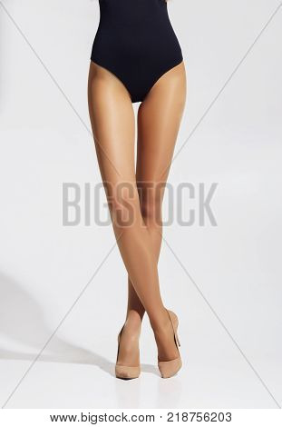 Fit and beautiful legs in sexy pantyhose. Woman in hosiery ovr grey background. poster