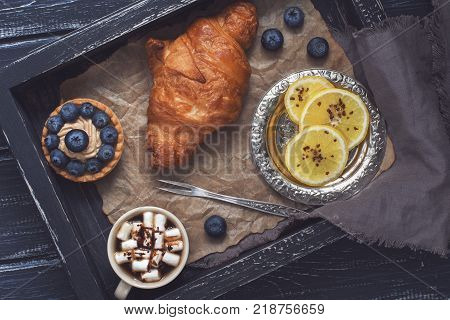 Croissant and cake with blueberries on a wooden tray. Lemon and vintage fork for lemon. Photo with toning