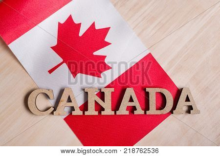Flag of Canada, the word Canada in wooden abstract letters, wooden background
