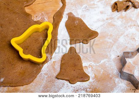 Preparing Christmas gingerbread cookies. Gingerbread dough and cookies ingredients. Ring bells shape