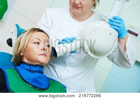 dentist operates dental intraoral x-ray unit for tooth image with patient