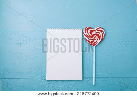 Blank note pad for text lollipop heart. blue table