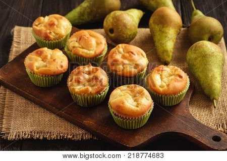 Homemade sweet muffins with pear stuffing on wooden background.