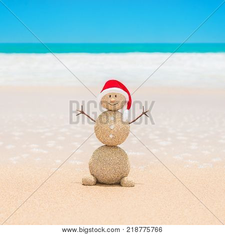 Positive sandy Snowman in red Santa hat at beach sand against ocean waves. Happy New Year and Merry Christmas holidays vacation in hot countries concept