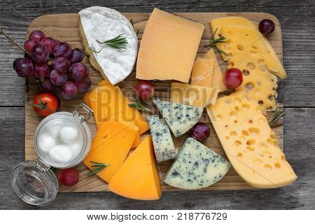 Assorted cheeses on wooden cutting board. Camembert cheese cheddar hard cheese slices sof cheese walnuts grapes tomatoes and rosemary. top view