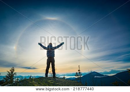 The boy hiker standing with raised hands on a top of mountain and enjoy the halo phenomenon in a sky. poster
