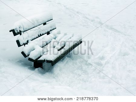 Winter wether nature snowy bench landscape with footsteps