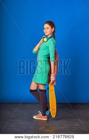 Girl loves to listen to the song in the phone.Elegant happy girl in big headphones and a skateboard isolated on a blue background.Sporty pretty teen girl loves sports.