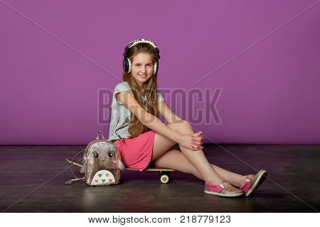 Girl teenager loves to listen to songs.Sporty pretty teen girl loves sports.Happy attractive young teen girl sitting on skateboard listening to your favorite music with headphones on purple background in the Studio.