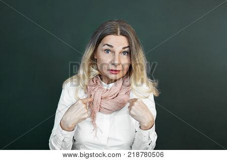 Waist up studio portrait of emotional astonished confused 50 year old European female having uncertain questioning facial expression pointing fingers at herself while being blamed for something
