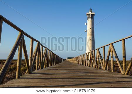 Wooden footbridge walkway to beach near Morro Jable lighthouse in warm sunset light, Fuerteventura island, Spain .