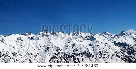 Panorama of snow covered mountains and blue sky at sun cold day. View from region Dombay Caucasus Mountains in winter.