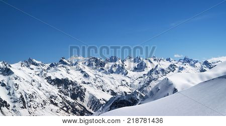 Panorama of snow-capped mountains with mount Elbrus at background and off-piste snowy for freeride at sun cold day. View from region Dombay Caucasus Mountains in winter.