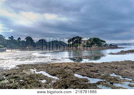Medieval castle on the shore of an atlantic ocean beach in Galicia Spain. With access bridge and very low tide. Dramatic sky covered with clouds and very calm waters