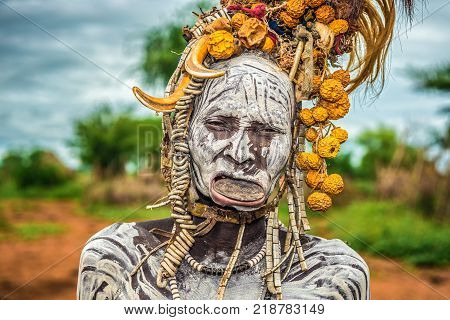 OMO VALLEY, ETHIOPIA - MAY 7, 2015 : Old woman from the african tribe Mursi with lip plate in her village.