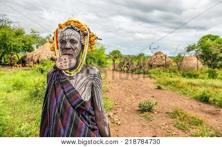 OMO VALLEY, ETHIOPIA - MAY 7, 2015 : Woman from the african tribe Mursi with big lip plate in her village.