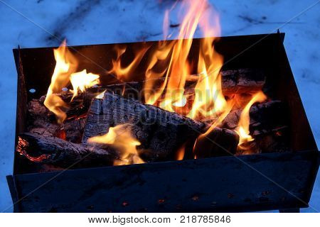 Background of fire and black wood. Dark grey black white coals on bright fire inside metal brazier. Wood burning in the brazier. Flames fire. Preparation for cooking barbecue.