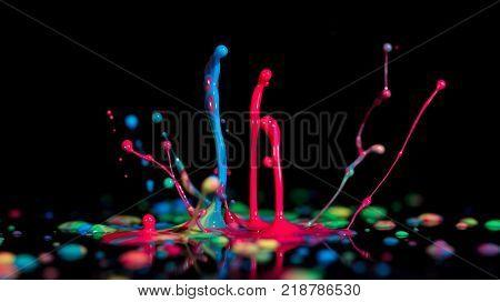 Splash of colorful liquid paint on a black background paint splash on black background