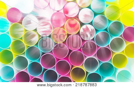 Many colorful straws stacked on top of each other. Beyond the straw penetrates the white light across the straw.