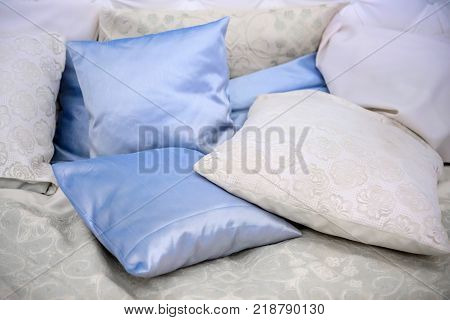 Pillow satin pile.  Bed for relaxation.  Bedding accessories for sleep. Pillows bedding colorful.