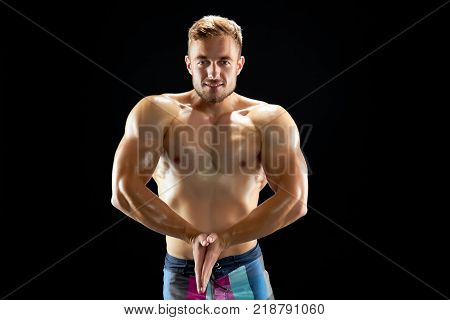 Athletic man demonstrating his toned muscles on black. Result of intense and persistence workout. Sport and success.