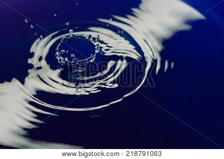 Beautiful splash of water drop. Freeze action. High-speed shooting of water drop. Beautiful drops of stop time, water splashing close up. Crystal clear water waves, drops and sprays. Crown
