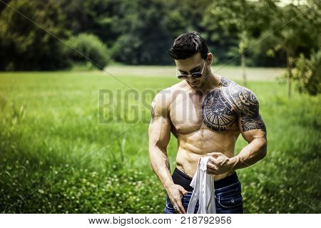 Handsome Muscular Shirtless Hunk Man Outdoor in City Park Standing on Grass. Showing Healthy Muscle Body While Looking away