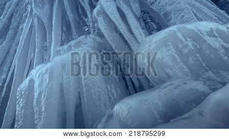 Frozen waterfall stream. Vertical slippery steep ice wall with long icicles.