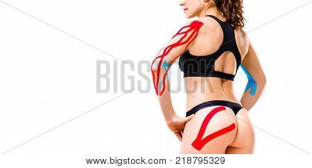 kinesiology tape concept rehabilitation sport and health.Close up of the buttock muscle of ass elastic and muscular and hands of a caucasian woman with a perfect figure on a white isolated background