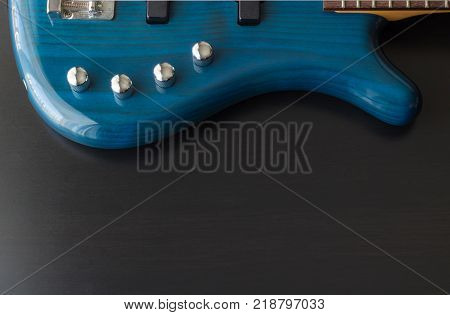 A blue five string bass guitar is strategically positioned in the frame with a black wooden background. The guitar has silver accessories and black pick-ups.