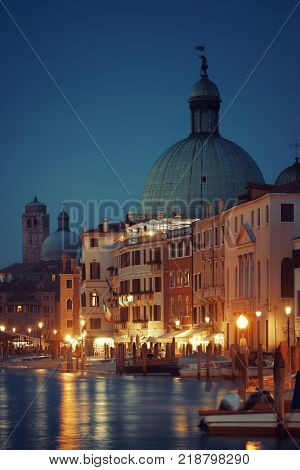 Venice canal view at night with San Simeone Piccolo church and historical buildings. Italy.