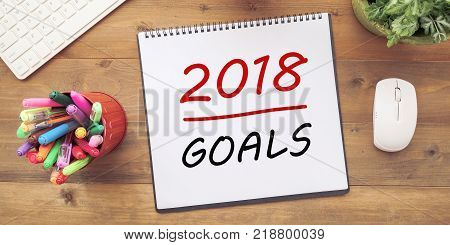2018 goals on notebook paper at office desk background banner sign business new year aim to success in business